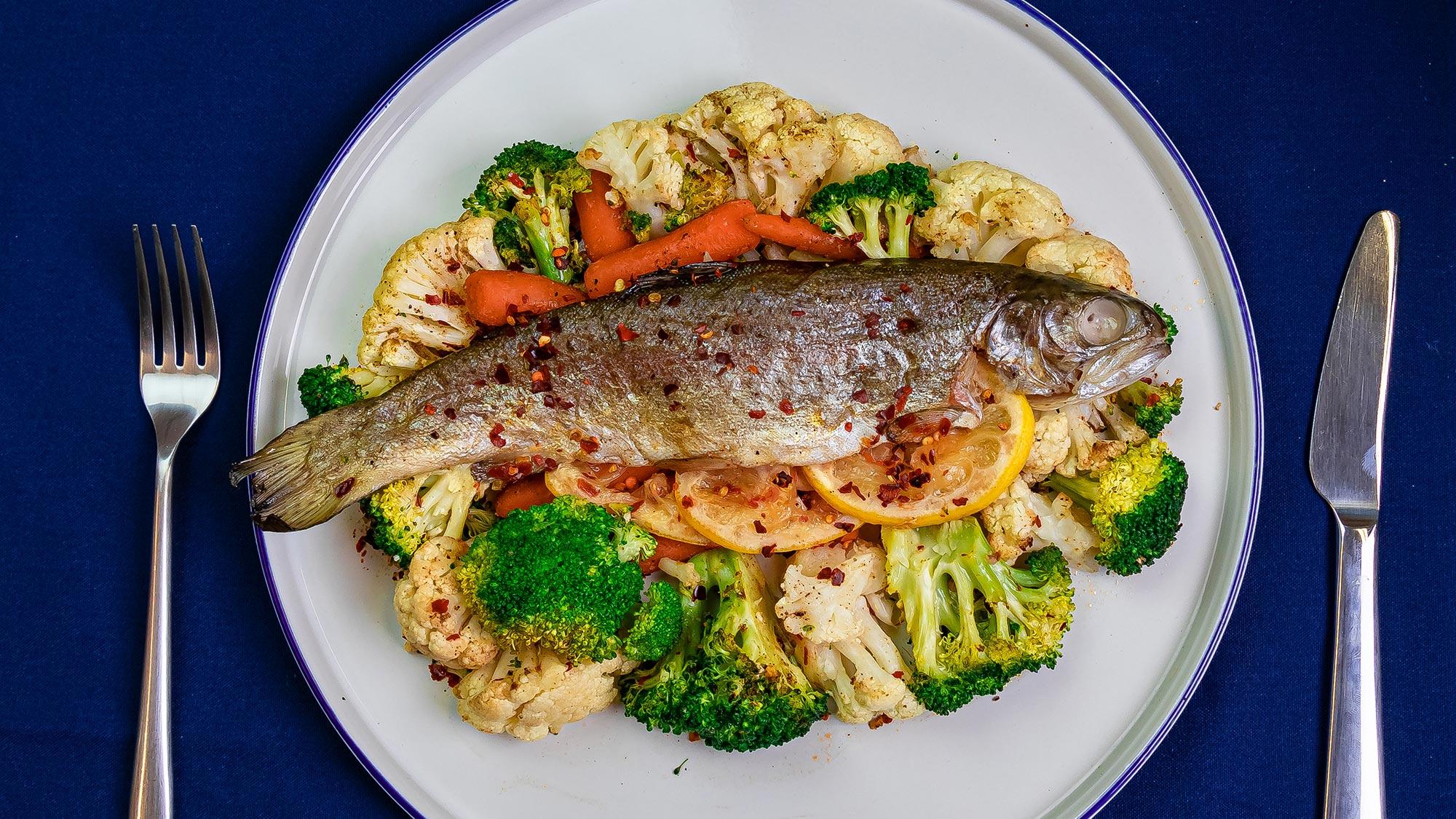 Hele forel uit de oven met bloemkool, wortelen en broccoli